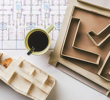 Architects in London drawings and model with coffee